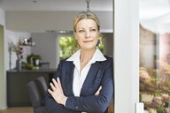 Portrait of confident businesswoman leaning against French door at home - PDF01768
