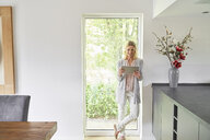 Smiling woman standing at French door using tablet at home - PDF01774