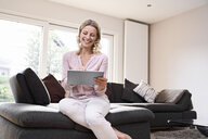 Happy woman sitting on couch using tablet at home - PDF01777