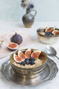 Bowl of porridge with sliced figs, blueberries and dried berries - JUNF01386