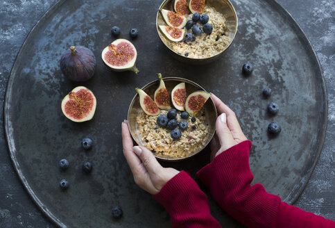 Woman's hands holding bowl of porridge with sliced figs, blueberries and dried berries - JUNF01389