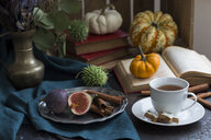 Autumnal still life with figs, cinnamon sticks, books and a cup of tea - JUNF01398