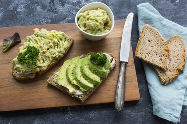 Slices of bread with sliced avocado and avocado cream on wooden board - JUNF01411