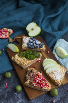 Bread slices with various toppings on wooden board - JUNF01423