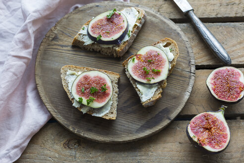 Buttered slices of bread with sliced figs on wooden plate - JUNF01426