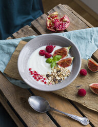 Bowl of natural yoghurt with fruit muesli, raspberries, figs and pomegranate seed - JUNF01429