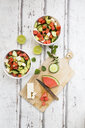 Watermelon salad with feta, cucumber, mint and lime dressing on white wood - LVF07448