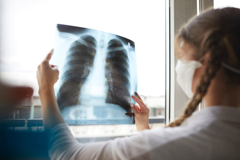 Young female doctor in front of window looking at hospital xray - CUF44202