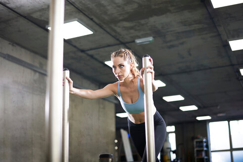 Woman doing sled training in gym - CUF44262