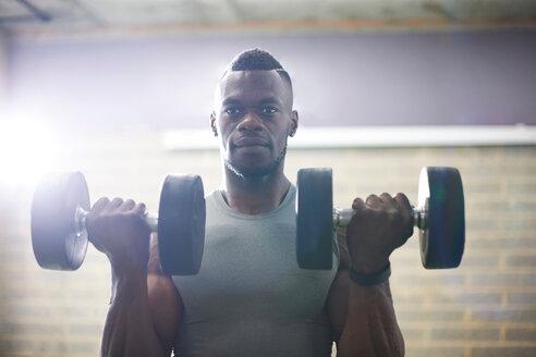 Man lifting dumbbells in gym - CUF44268