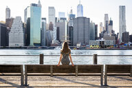 USA, New York, Brooklyn, back view of woman sitting on bench in front of East River and skyline of Manhattan - GIOF04571