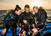 Friends looking at images on underwater camera after dive, Tubbataha Reefs Natural Park, Sulu Sea, Philippines - CUF44280