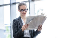 Businesswoman reading newspaper in office - CUF44337