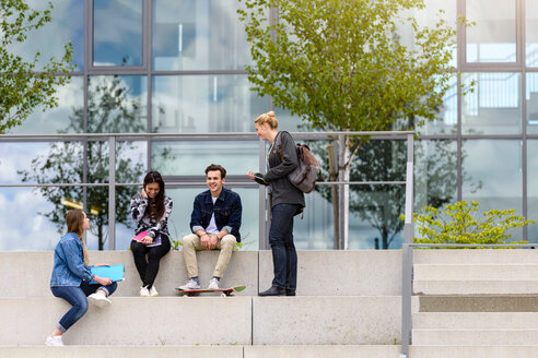 Four young adult students sitting chatting on stairway outside college - CUF44340