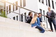 Four young adult students sitting chatting on stairway outside college, low angle view - CUF44343