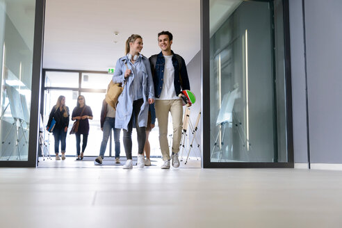 Students entering college building by glass doors - CUF44346