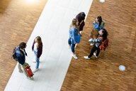 Male and female university students chatting in university lobby, high angle view - CUF44358
