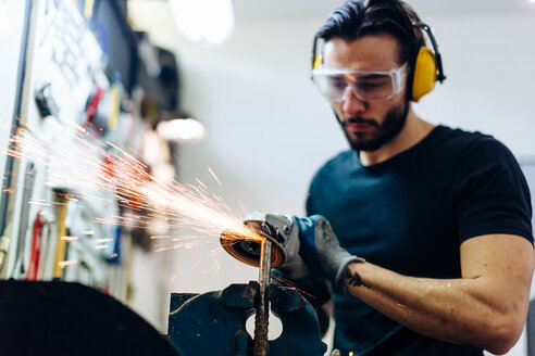 Young man using angle grinder on metal in workshop - CUF44430