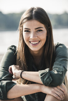 Portrait of smiling young woman sitting outdoors - UUF15317