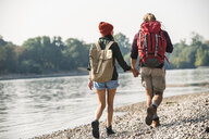 Rear view of young couple with backpacks walking hand in hand at the riverside - UUF15326