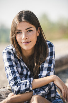 Portrait of smiling young woman sitting outdoors - UUF15341