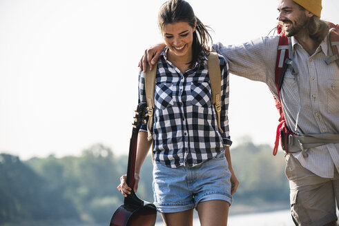 Happy young couple with backpacks and guitar outdoors - UUF15362