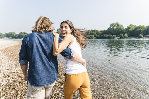 Happy young couple in love walking at the riverside - UUF15377