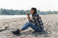Relaxed young woman holding a mug sitting at the riverside - UUF15407