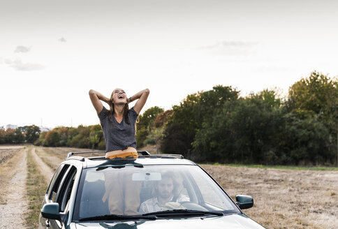Carefree young woman looking out of sunroof of a car - UUF15419