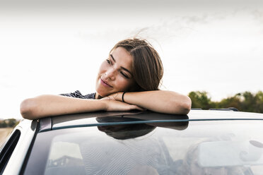 Smiling young woman looking out of sunroof of a car - UUF15422