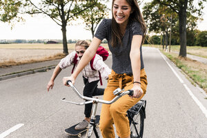 Happy young couple with bicycle and skateboard on country road - UUF15443