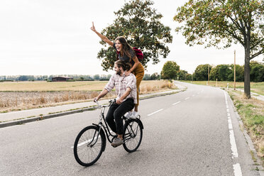 Happy young couple riding together on one bicycle on country road - UUF15446