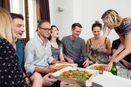 Group of friends chatting over drinks and pizza at home - CUF44540