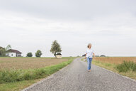 Mature woman walking on remote country lane in summer - JUNF01438