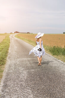 Rear view of mature woman walking on remote country lane in summer - JUNF01444