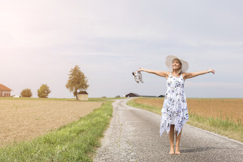 Mature woman standing on remote country lane in summer with outstretched arms - JUNF01447