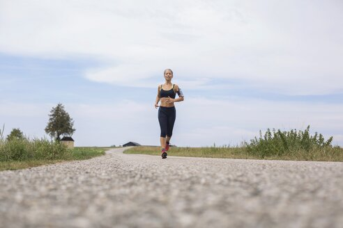 Mature woman running on remote country lane in summer - JUNF01456
