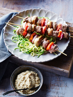 Lamb souvlaki skewers, with courgette noodles and baba ganoush, close-up - CUF44573