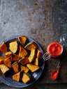 Still life of baked pumpkin on plate with jar of chilli sauce, overhead view - CUF44615