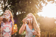 Girls blowing bubbles in park - CUF44717