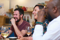 Friends laughing at dinner party - CUF44735