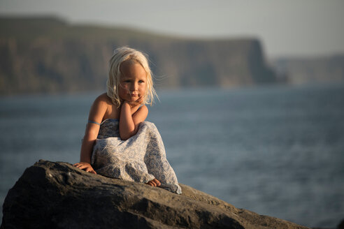 Portrait of young girl, sitting on rock, Doolin, Clare, Ireland - CUF44810