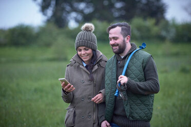Man and woman walking arm in arm across field looking at smartphone - CUF44954