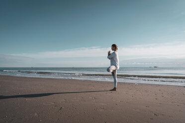 Woman practising yoga on beach - CUF44987