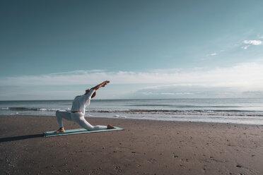 Woman practising yoga on beach - CUF44990
