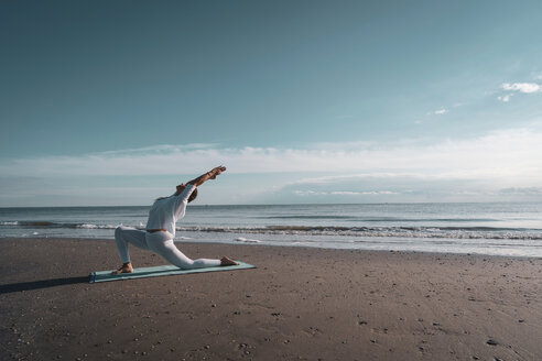 Woman practising yoga on beach - CUF44990