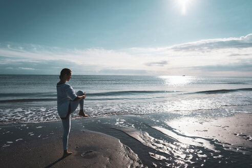 Woman practising yoga on beach - CUF44993