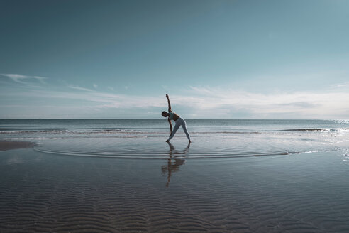 Woman practising yoga on beach - CUF44996
