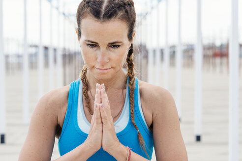 Woman practising yoga by beach - CUF44999
