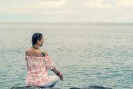 Woman meditating by sea - CUF45002